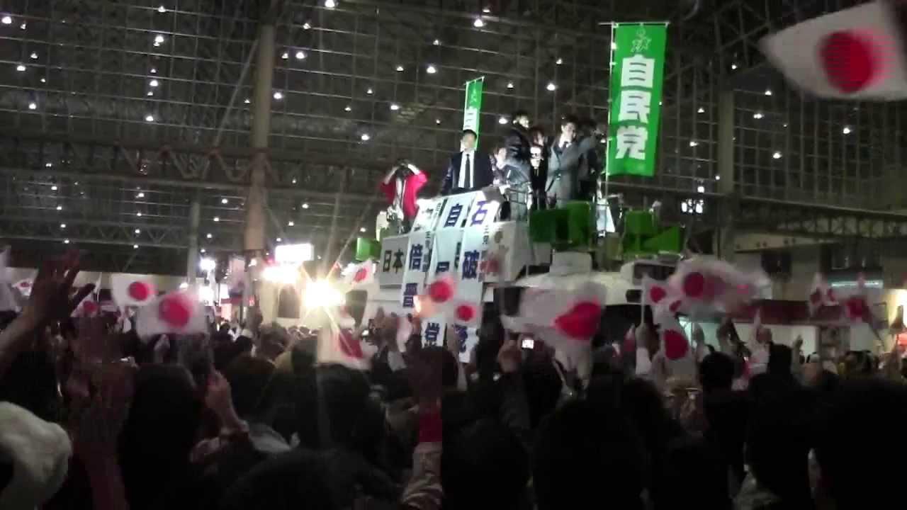 写真(日の丸で応援される安倍さん) 出典:YouTube安倍晋三内閣総理大臣 ニコニコ超会議での演説
