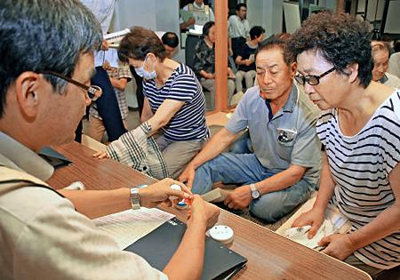 写真(ヨウ素剤の事前配布を受ける住民) 出典:京都新聞