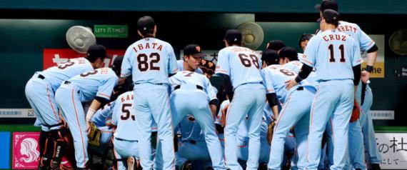 写真(円陣を組む巨人の選手たち) 出典:朝日新聞