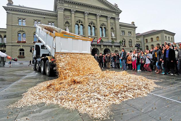 写真(ベーシックインカムの国民投票を行う予定のスイス。推進派の市民がスイス国会前に大量の硬貨を撒いた。) 出典:www.bloomberg.com