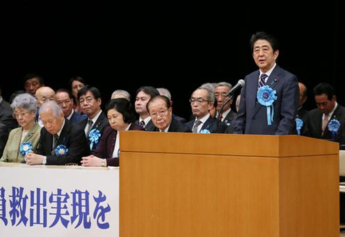 写真:「最終決戦は続いている 制裁と国際連携で全員救出実現を!国民大集会」に出席し、挨拶する安倍総理。出典:首相官邸ホームページ