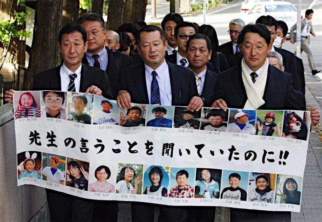 写真(大川小学校の津波訴訟判決を迎え、仙台地裁に入る原告遺族ら) 出典:時事ドットコム